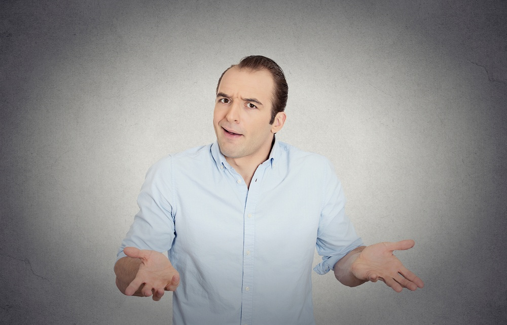 Closeup portrait of dumb clueless funny looking young man, arms out asking what's the problem who cares so what, I don't know, isolated grey wall background. Negative human emotions facial expressions