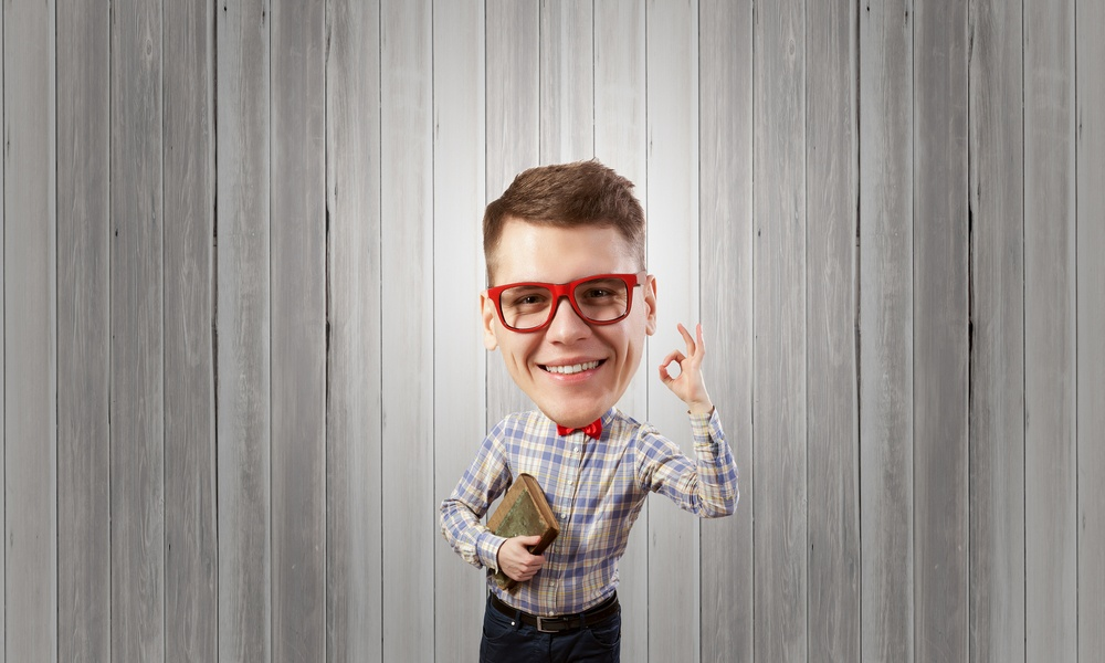 Young funny big headed man in glasses with book in hands showing ok gesture